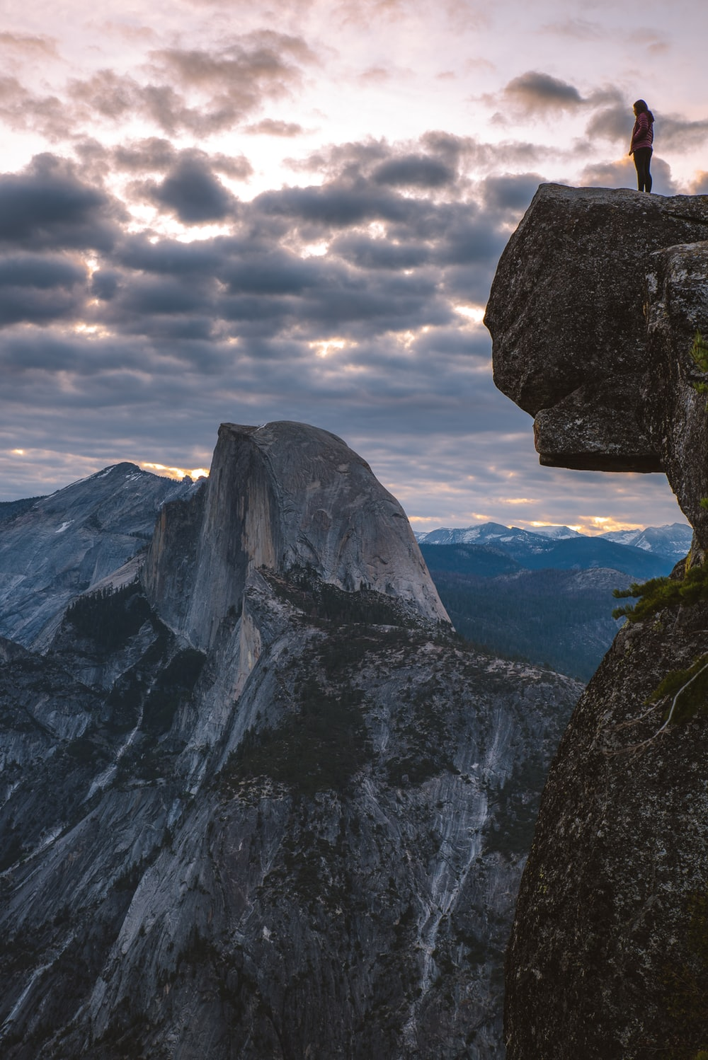 person standing on rocky mountain cliff