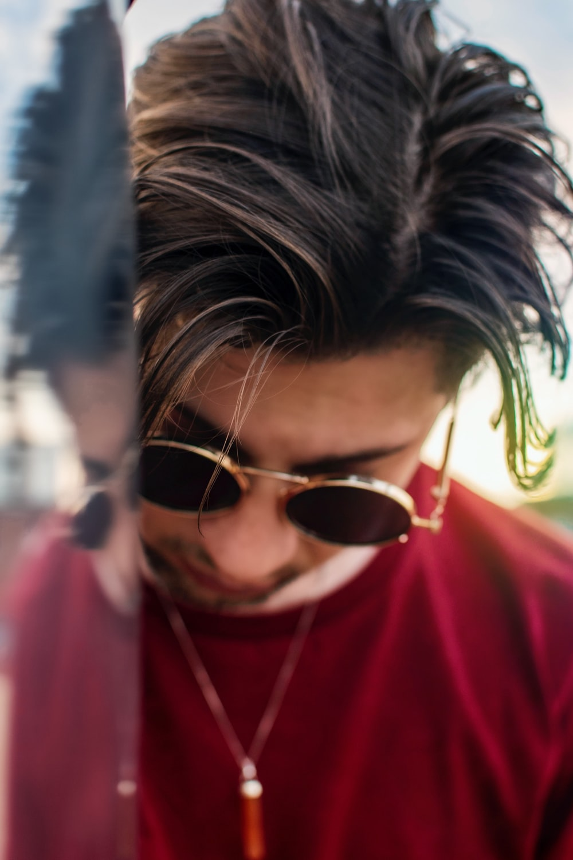 man wearing red shirt and round sunglasses