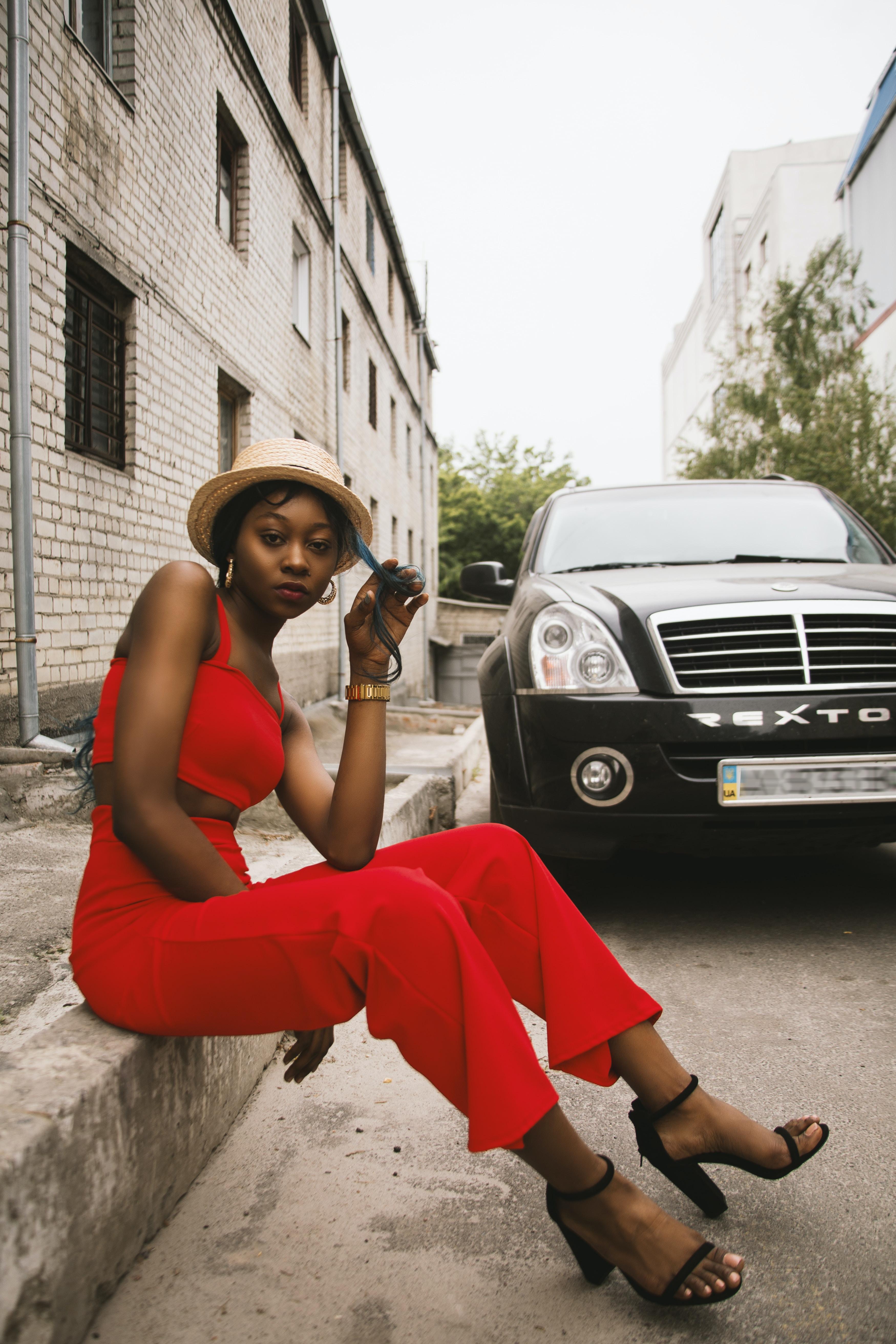 woman sitting on floor near black vehicle