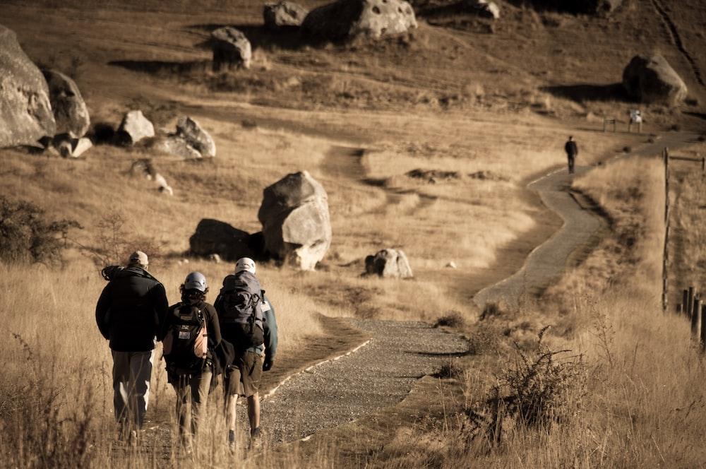 three person walking through road