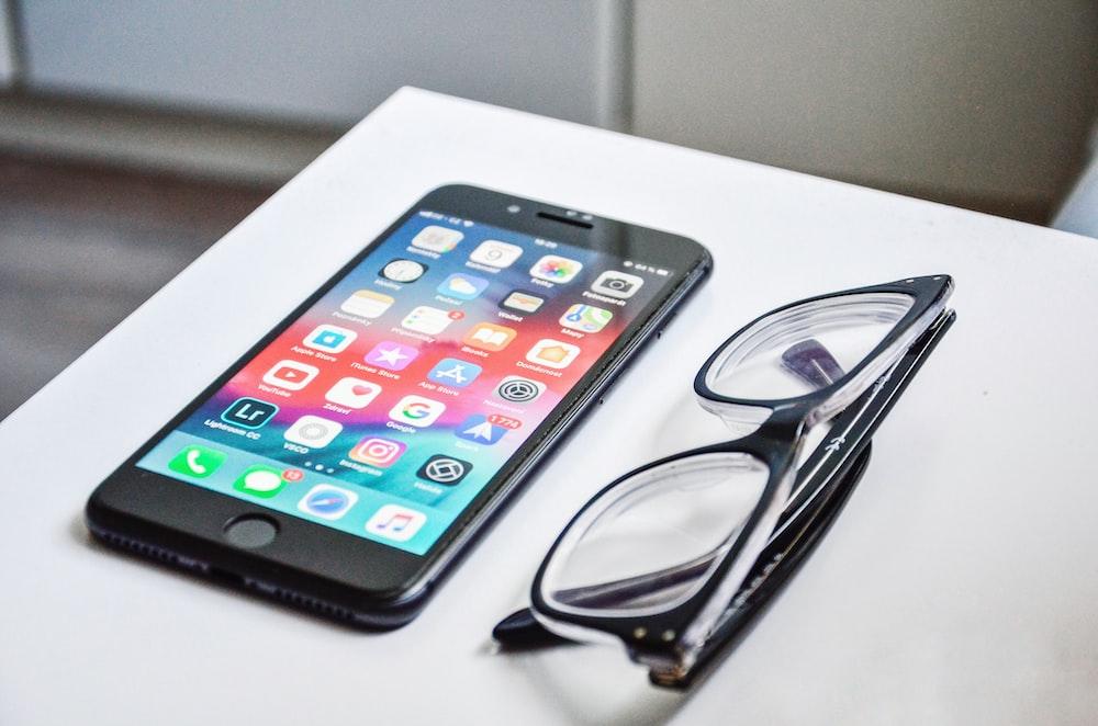 iPhone beside eyeglasses on desk