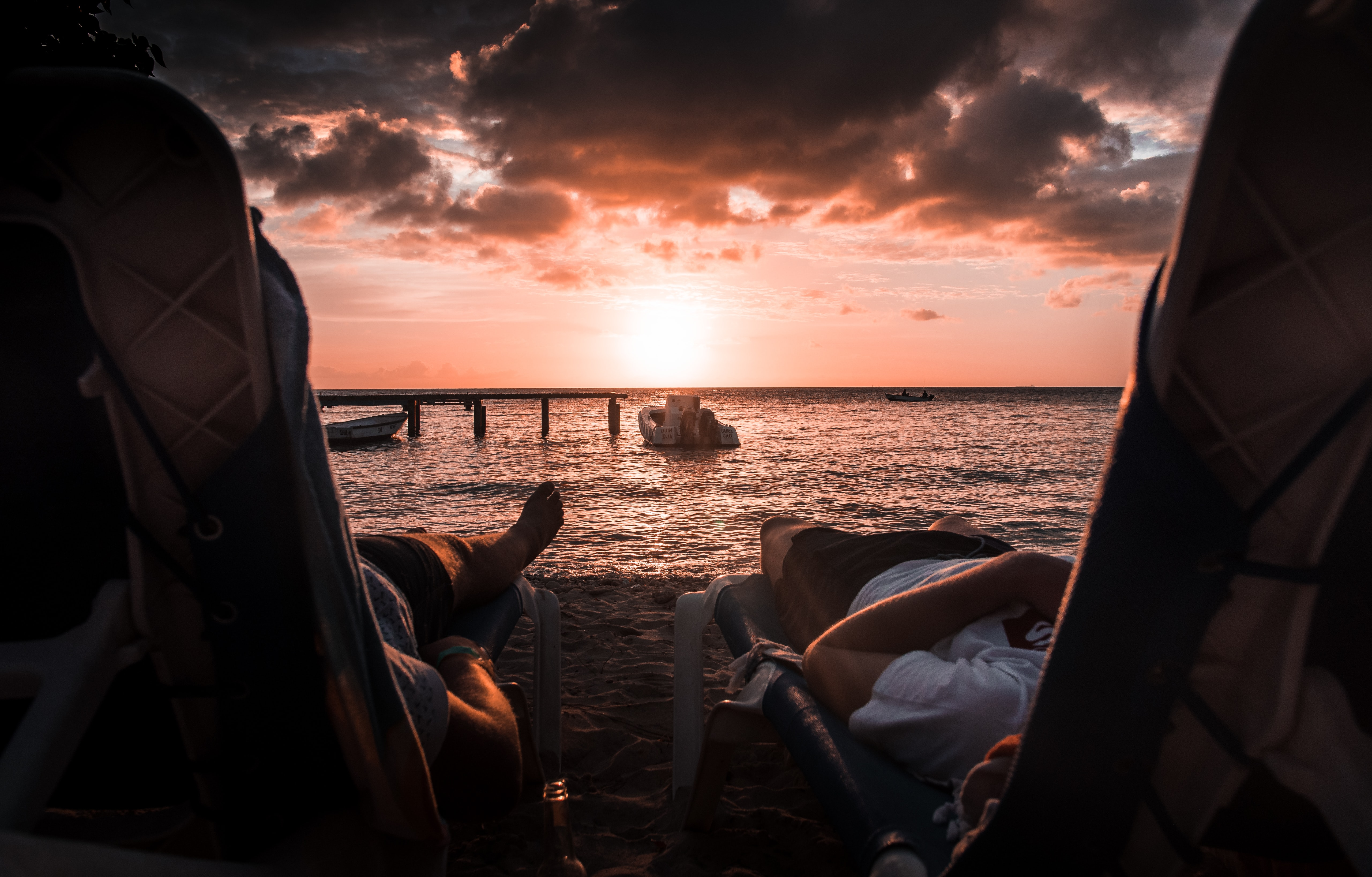 two person lying on chaise lounge under sunset