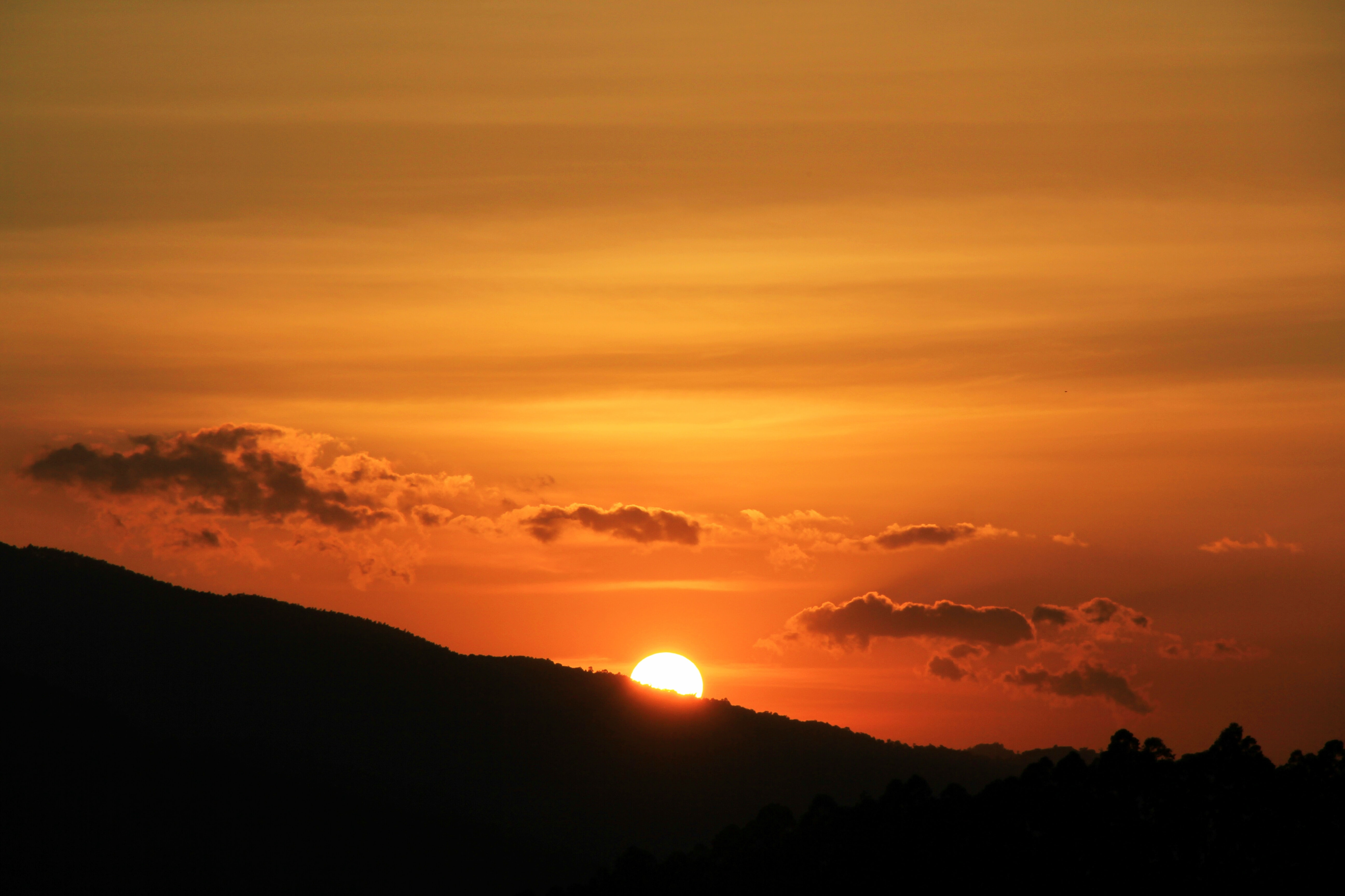 sun behind silhouette of a mountain