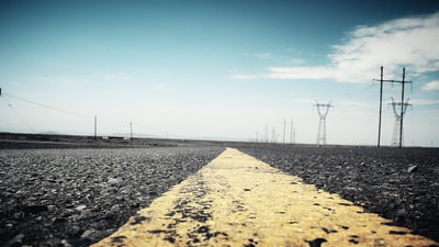 concrete road surrounded by electric posts line teams background