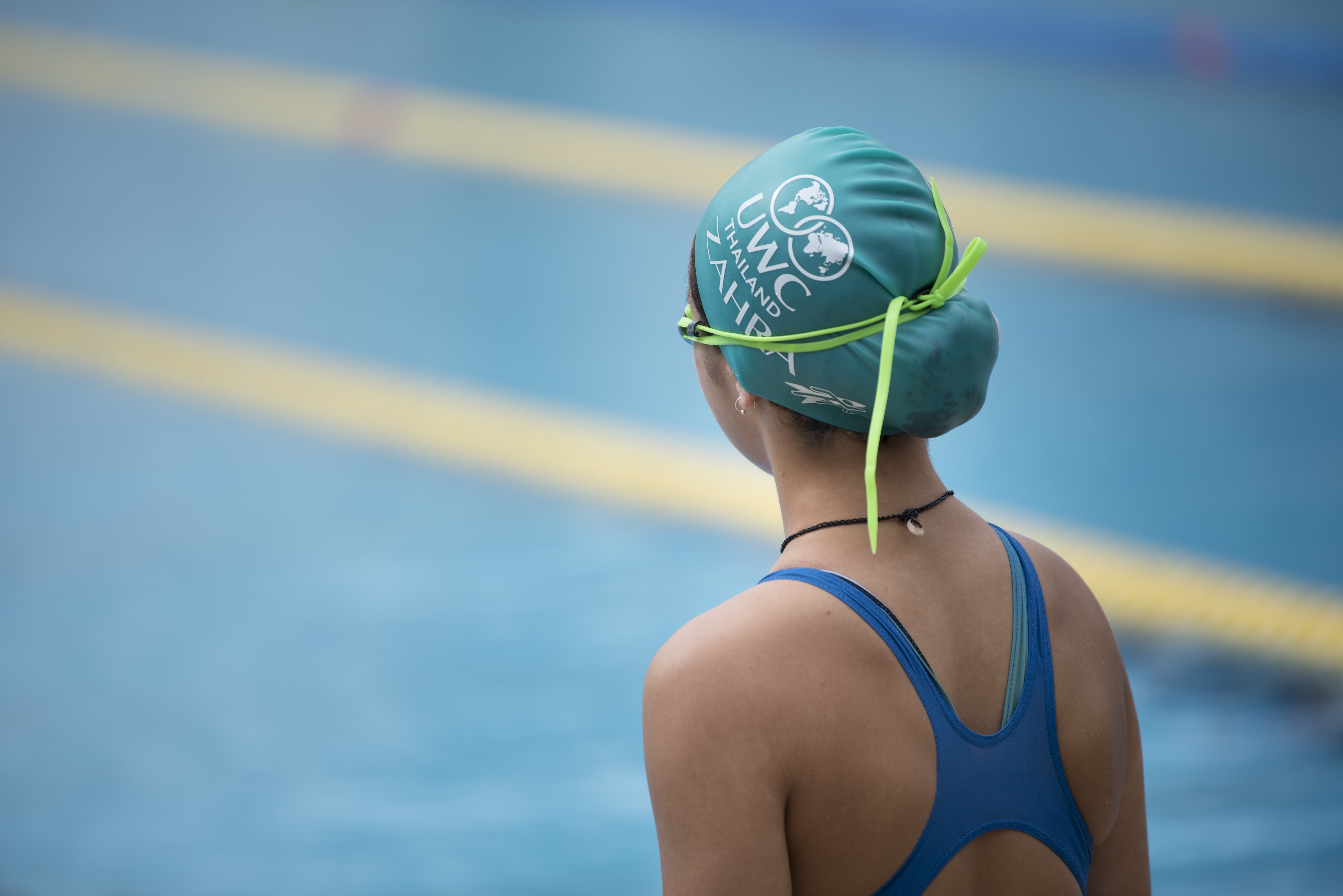 girl wearing swimsuit, swim cap, and swim goggles in front of swimming pool