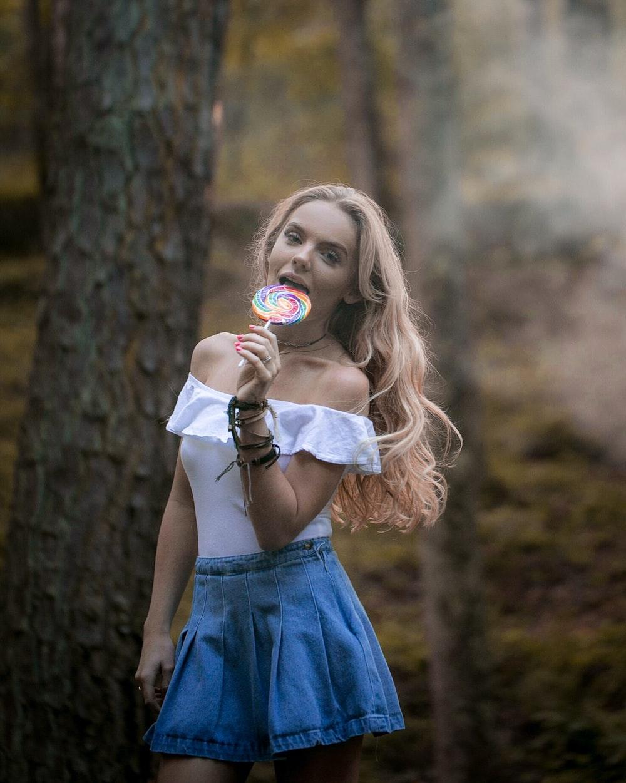 woman holding lollipop near the tree trunk