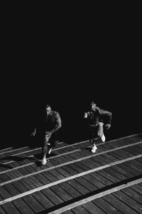 grayscale photo of two men racing each other