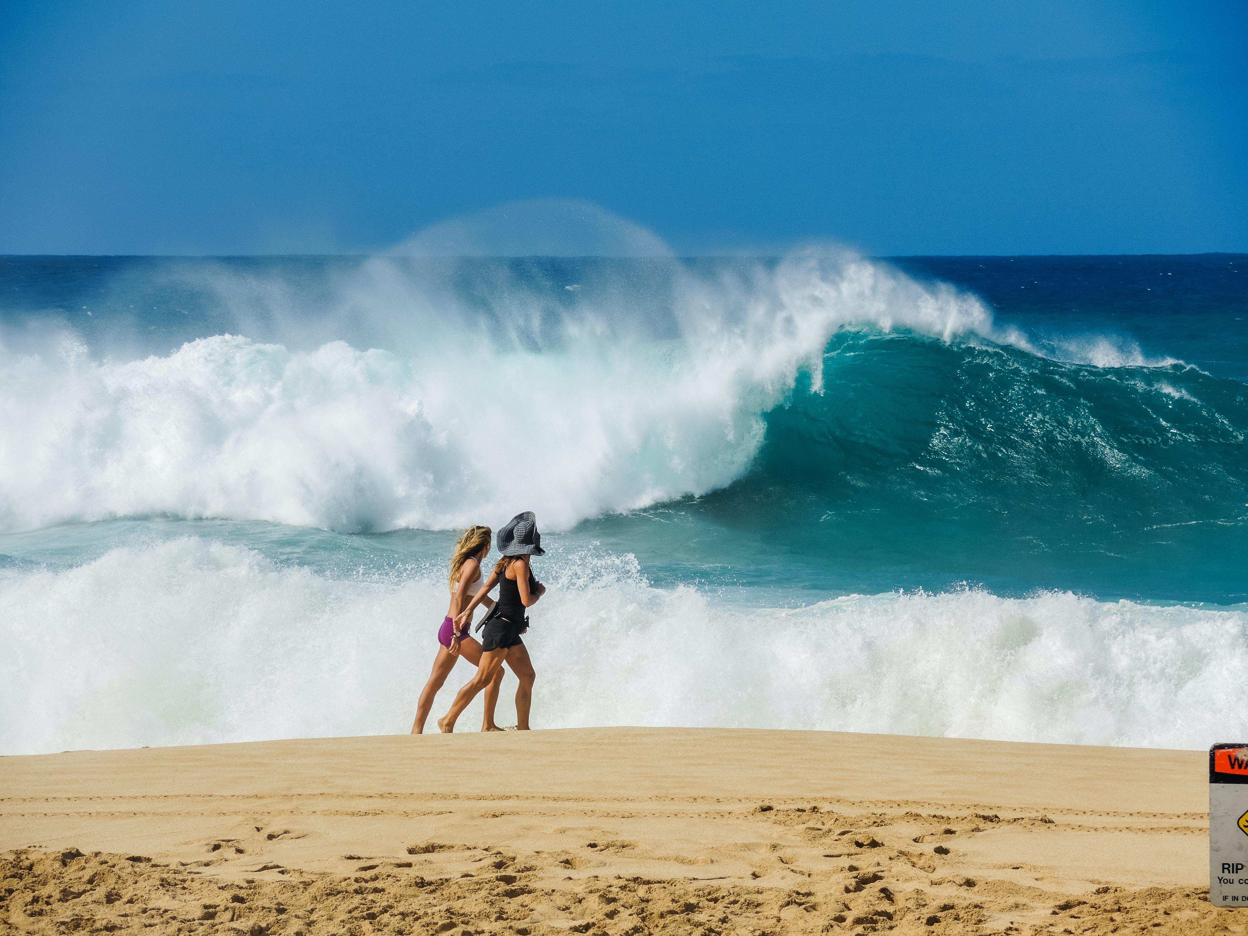 two women walking on shore