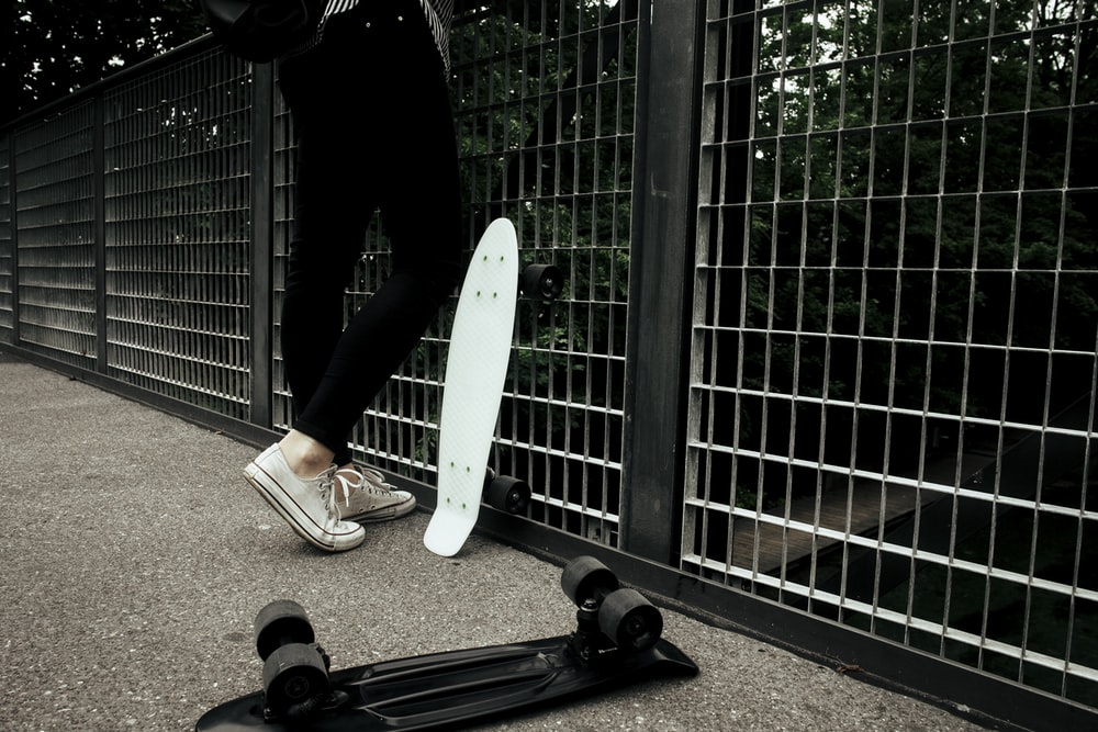 person standing near in front fence near penny board