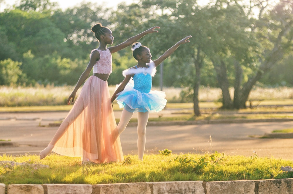 two girls wearing blue and peach dresses dancing on green grass