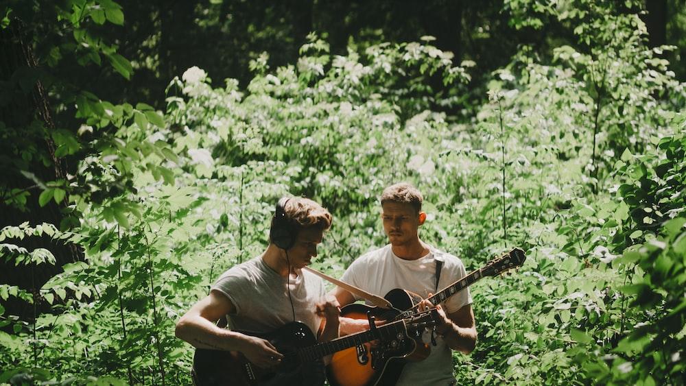 two men playing guitar