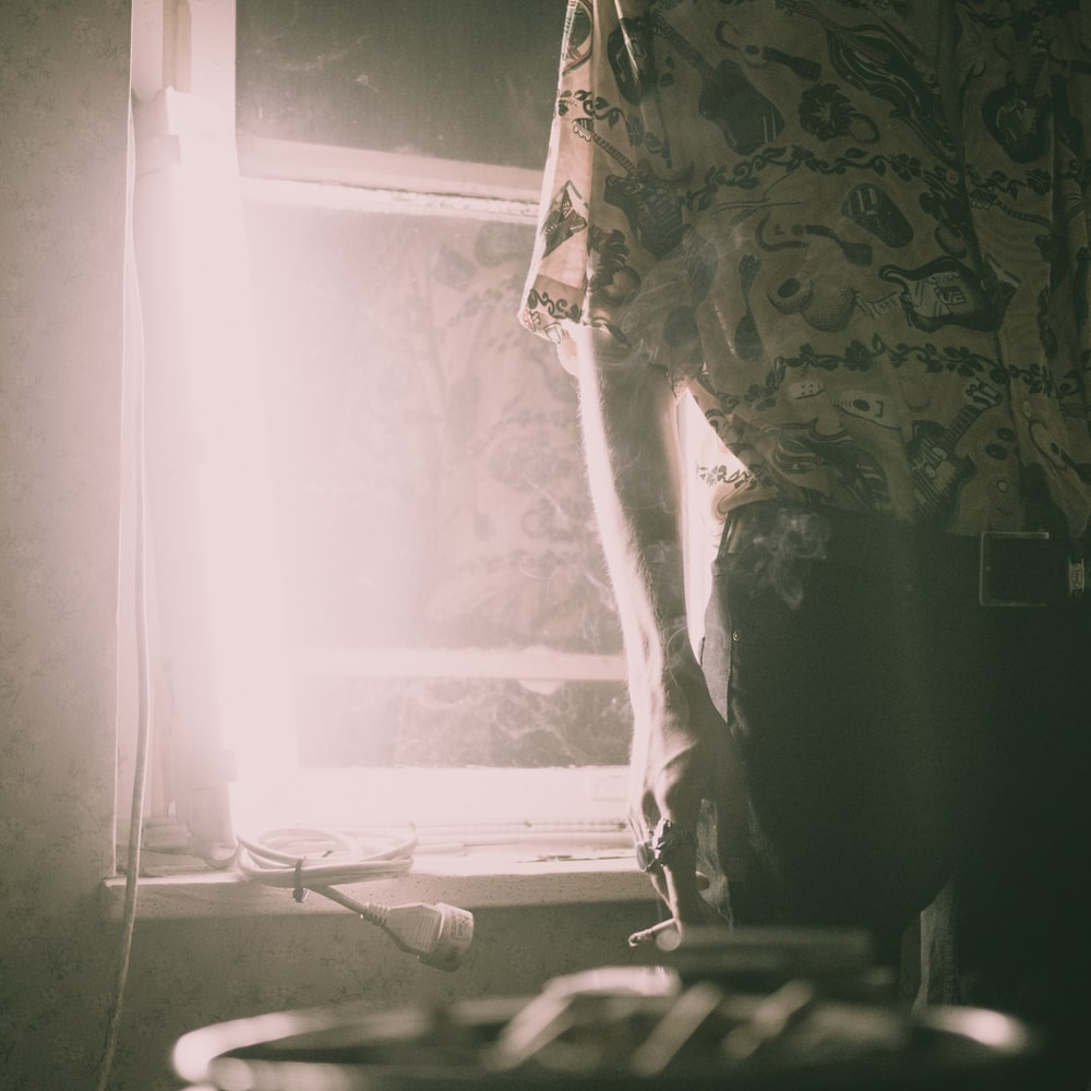 person holding cigarette standimg beside window inside the house