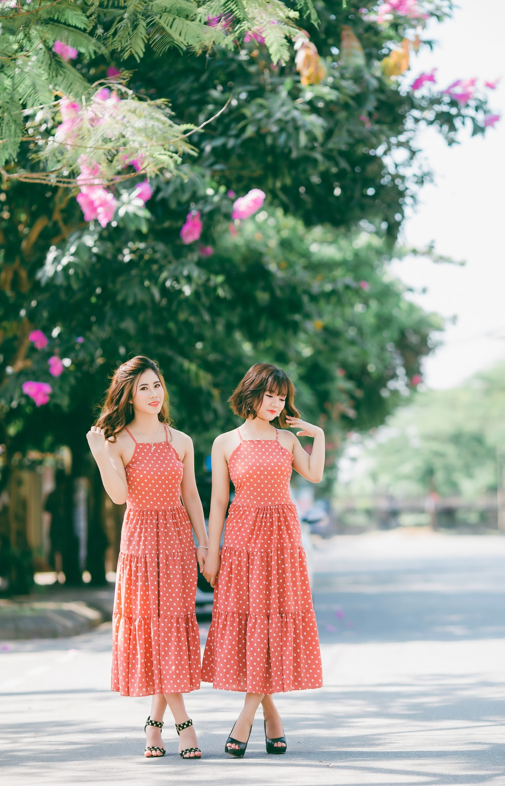 two women wearing red-and-white polka dot dresses standing on road near pink petaled flowers during daytime