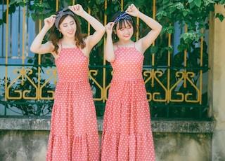 two women's wearing polka-dot dresses holding their turban headbands