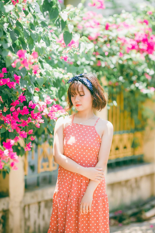 woman in orange polka-dot spaghetti strap dress standing near pink and green plants