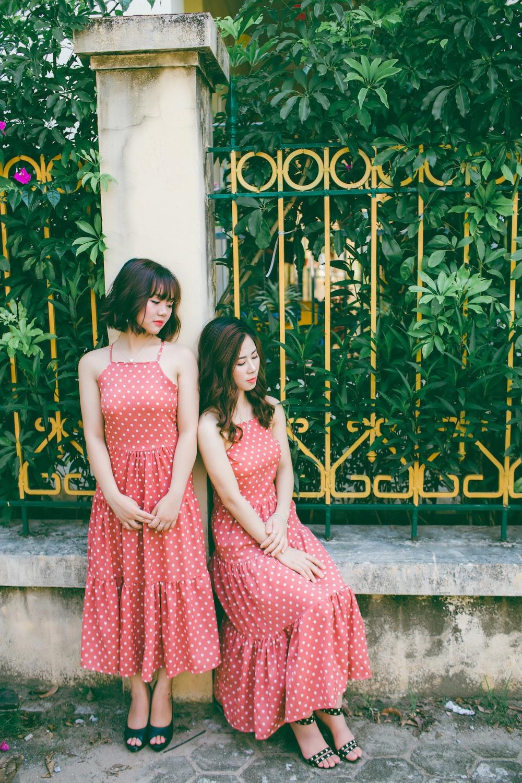 two women wearing red-and-white polka-dot spaghetti strap dress leaning on gray concrete pillar