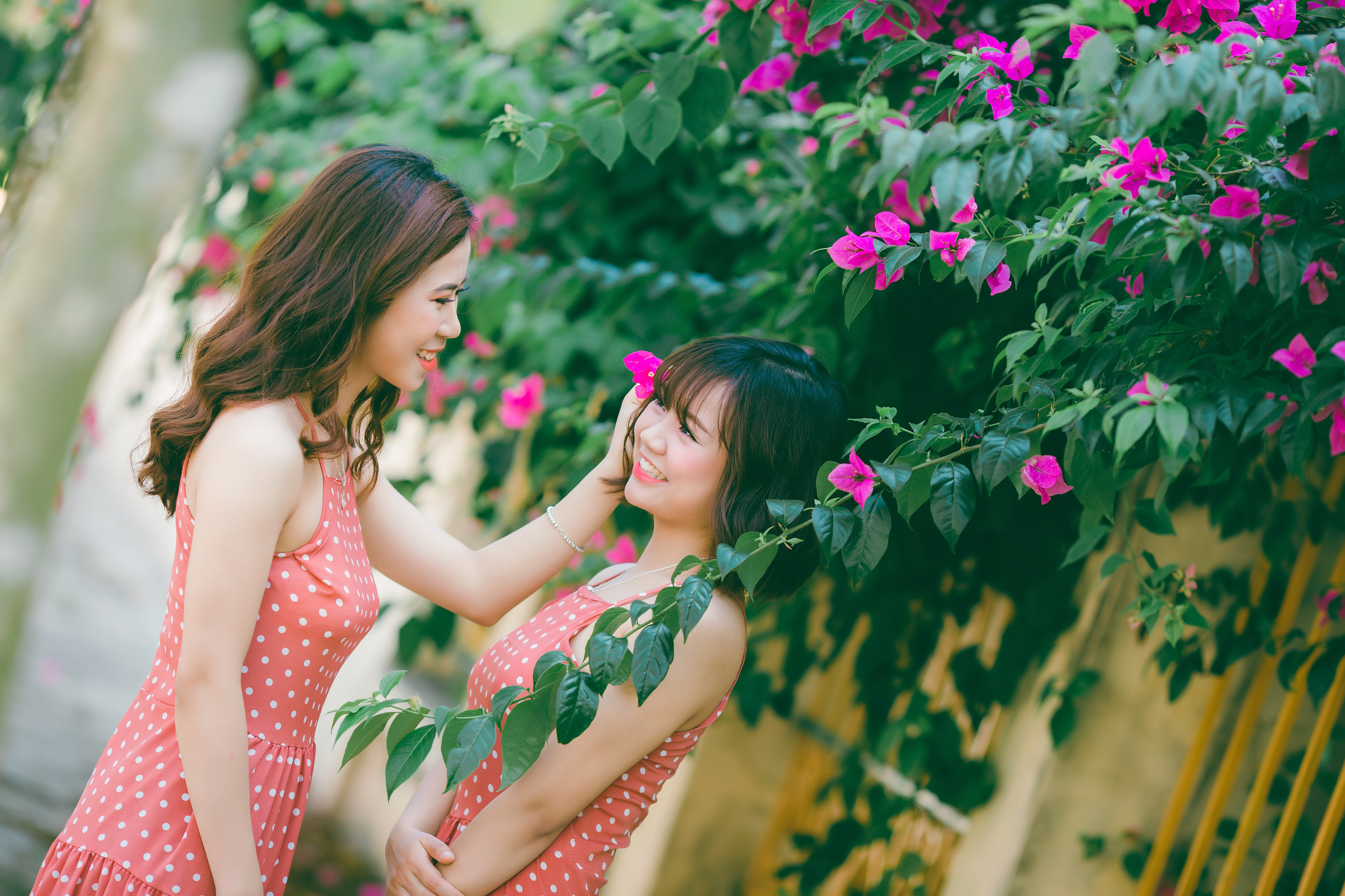 two women in dotted sleeveless shirt beside flowers