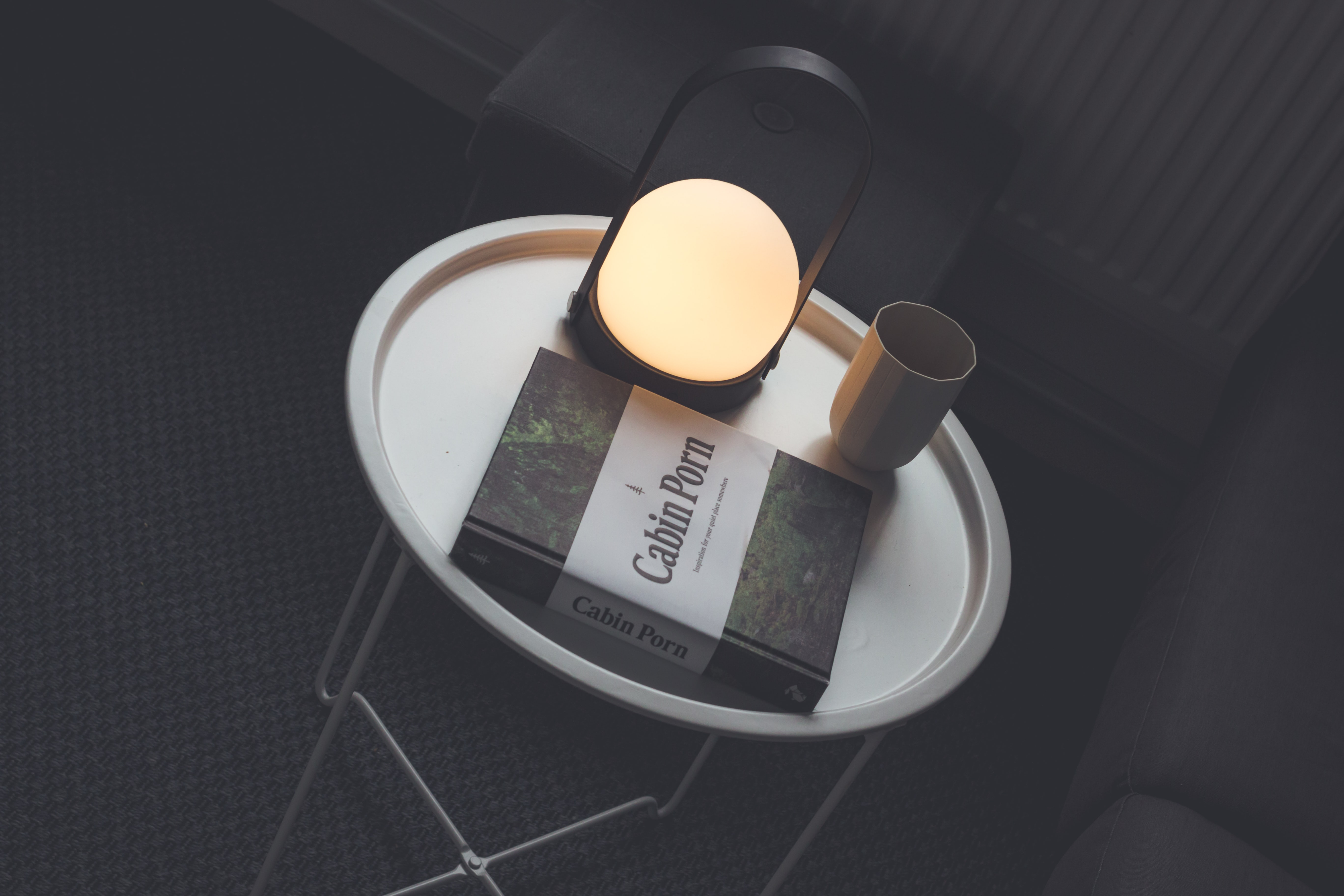 Cabin Porn book beside lamp and drinking cup on table
