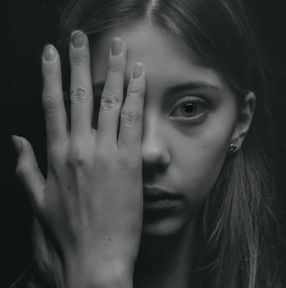 woman covering half of her face grayscale photography