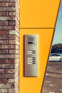 gray alarm system on yellow wall