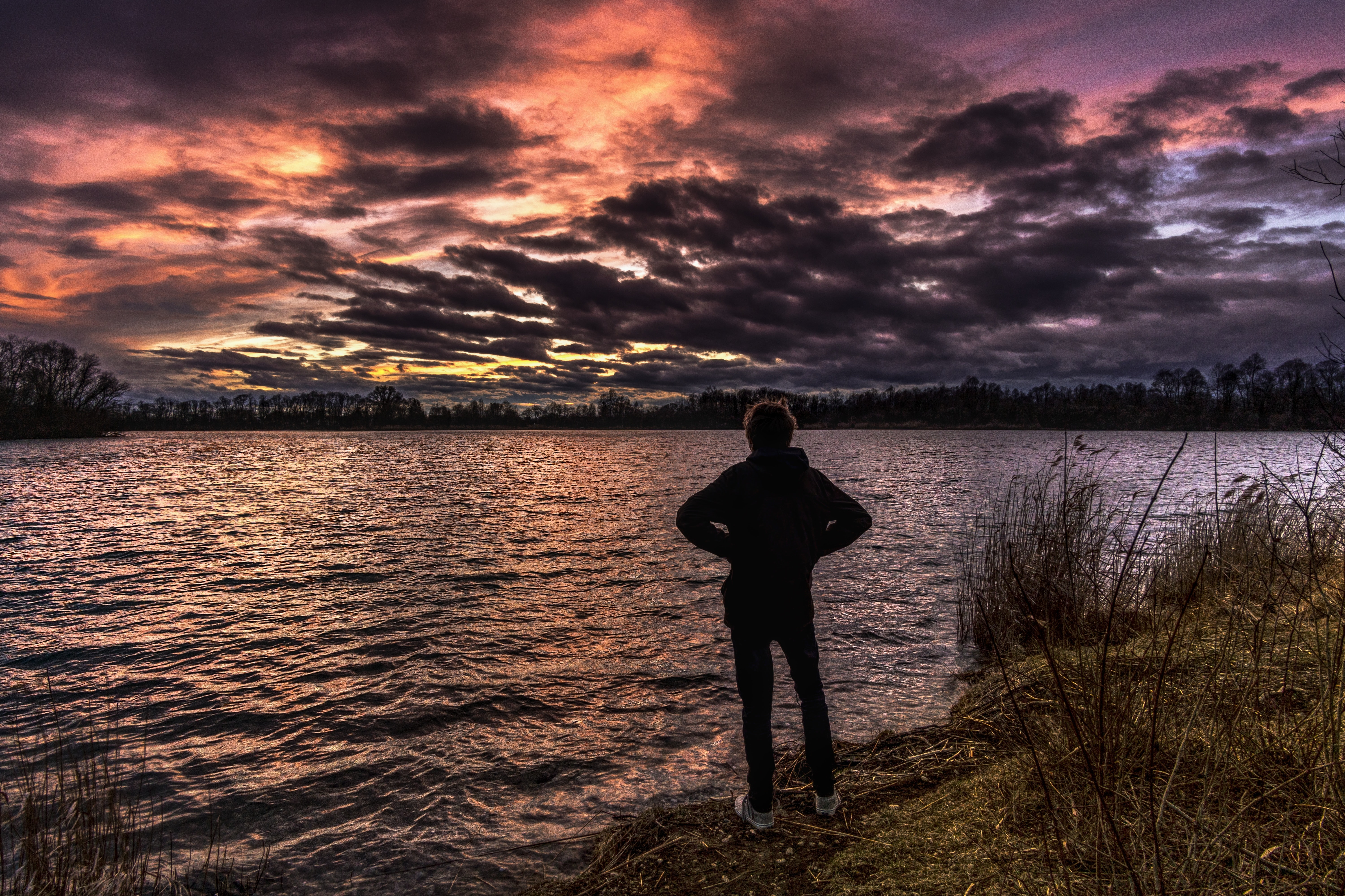 person standing near body of water during golden hour