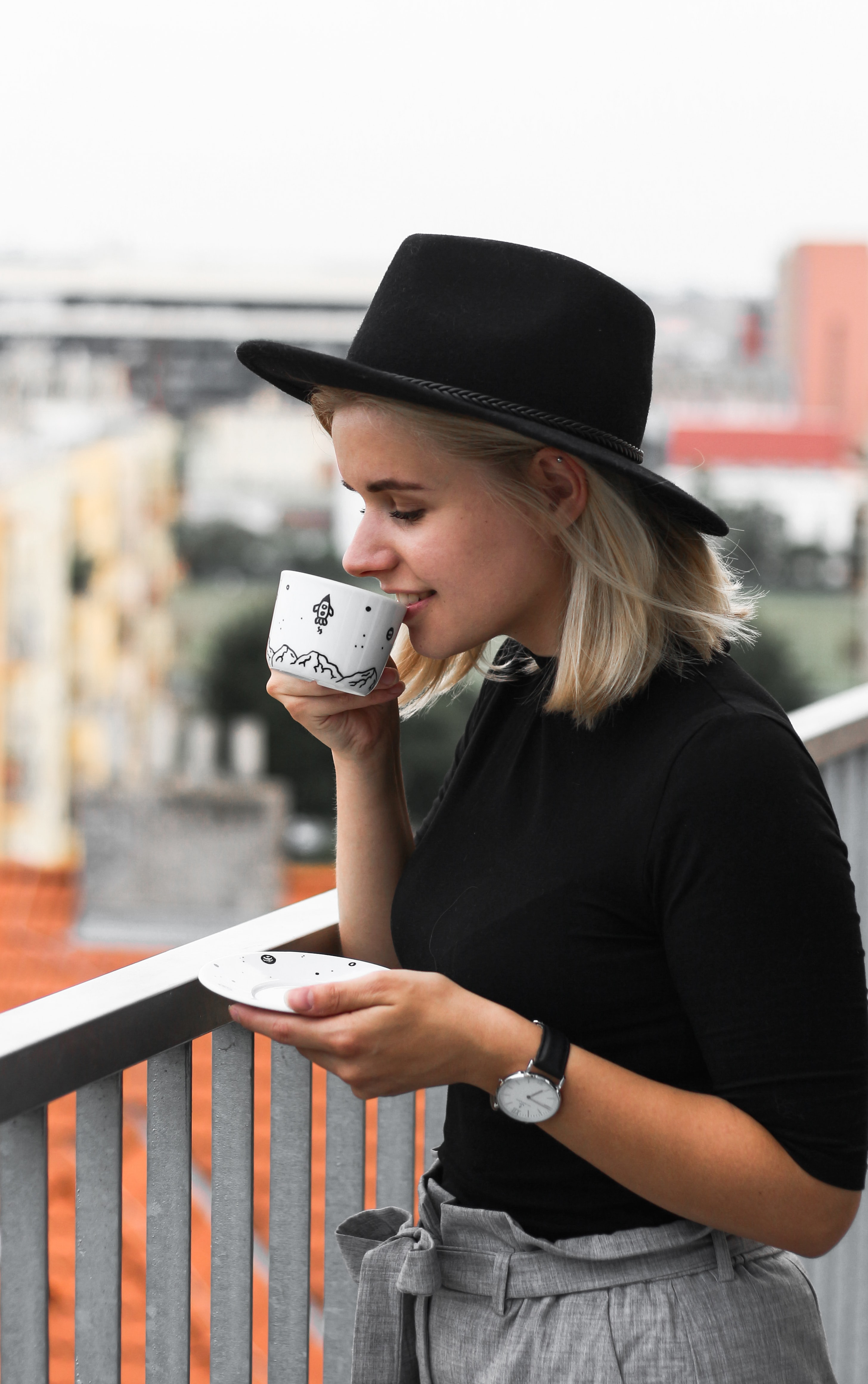 woman drinking on cup of coffee near railings