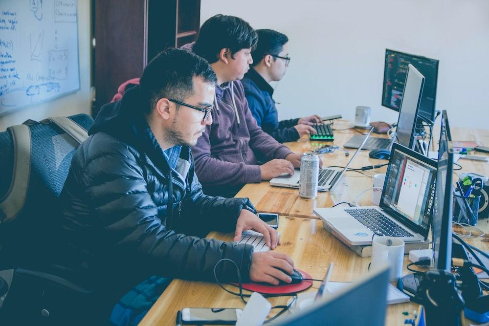 three men facing computer monitors