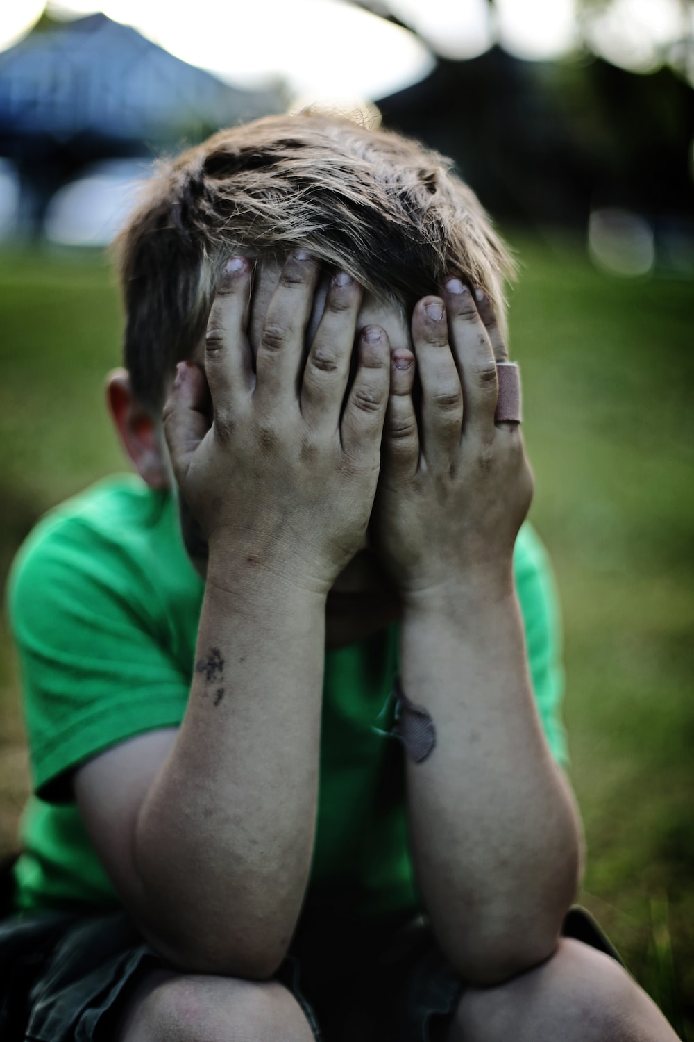boy sitting while covering his face