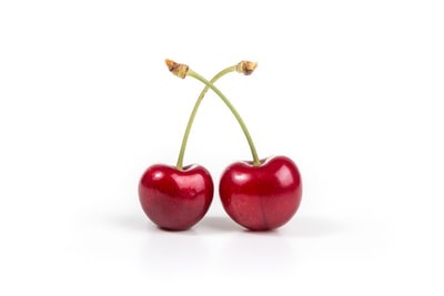 two cherries on white surface fruit teams background