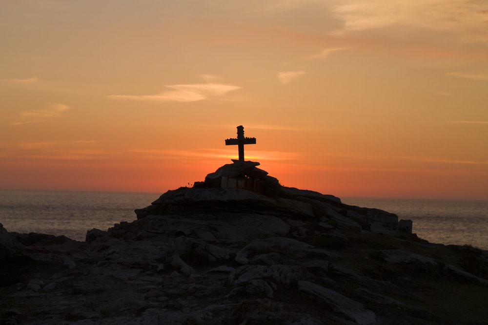 cross silhouette on mountain during golden hour