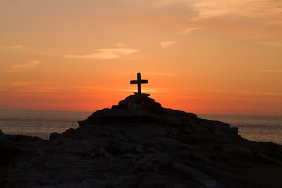 cross silhouette on mountain during golden hour religion teams background