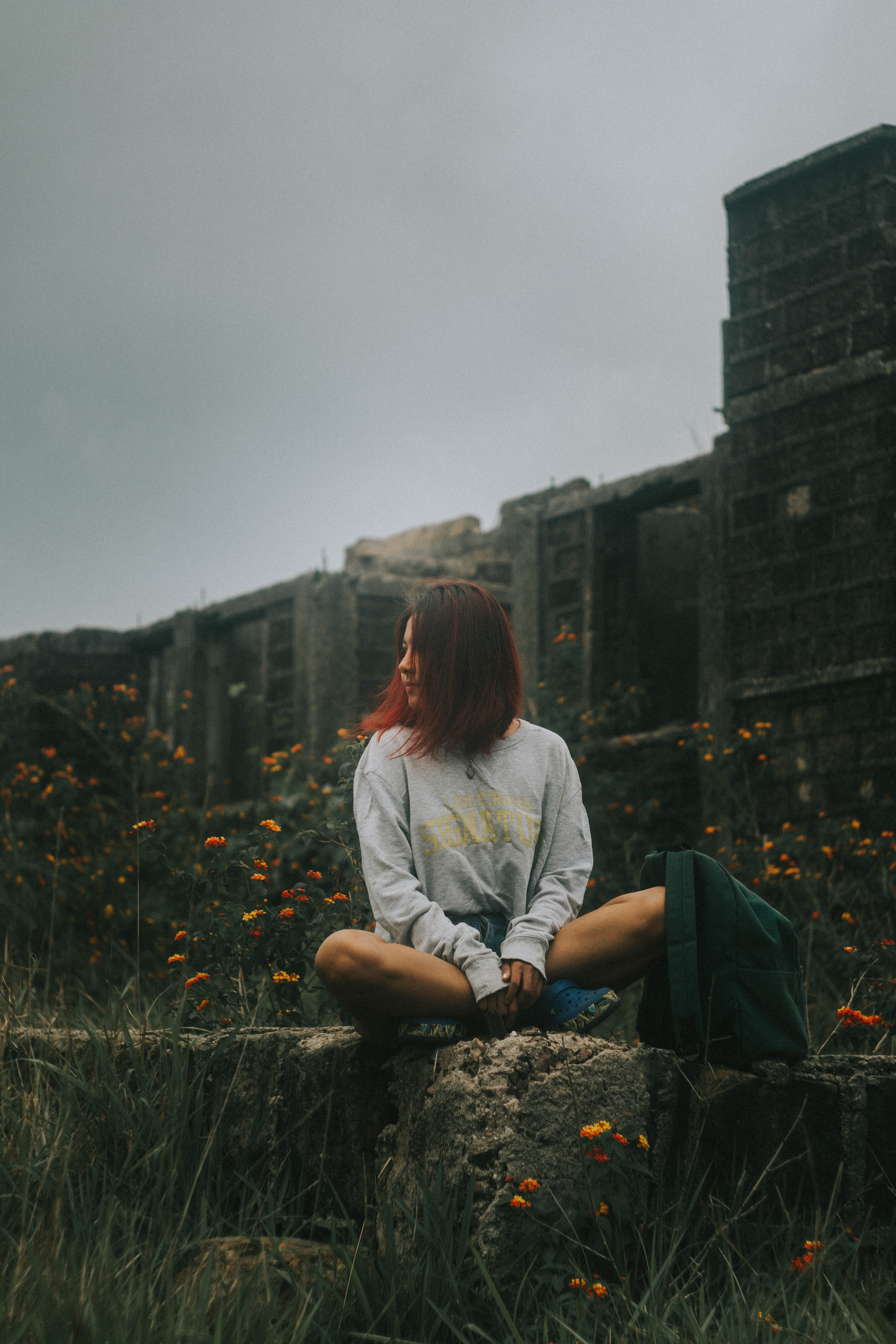 woman sitting on concrete fence