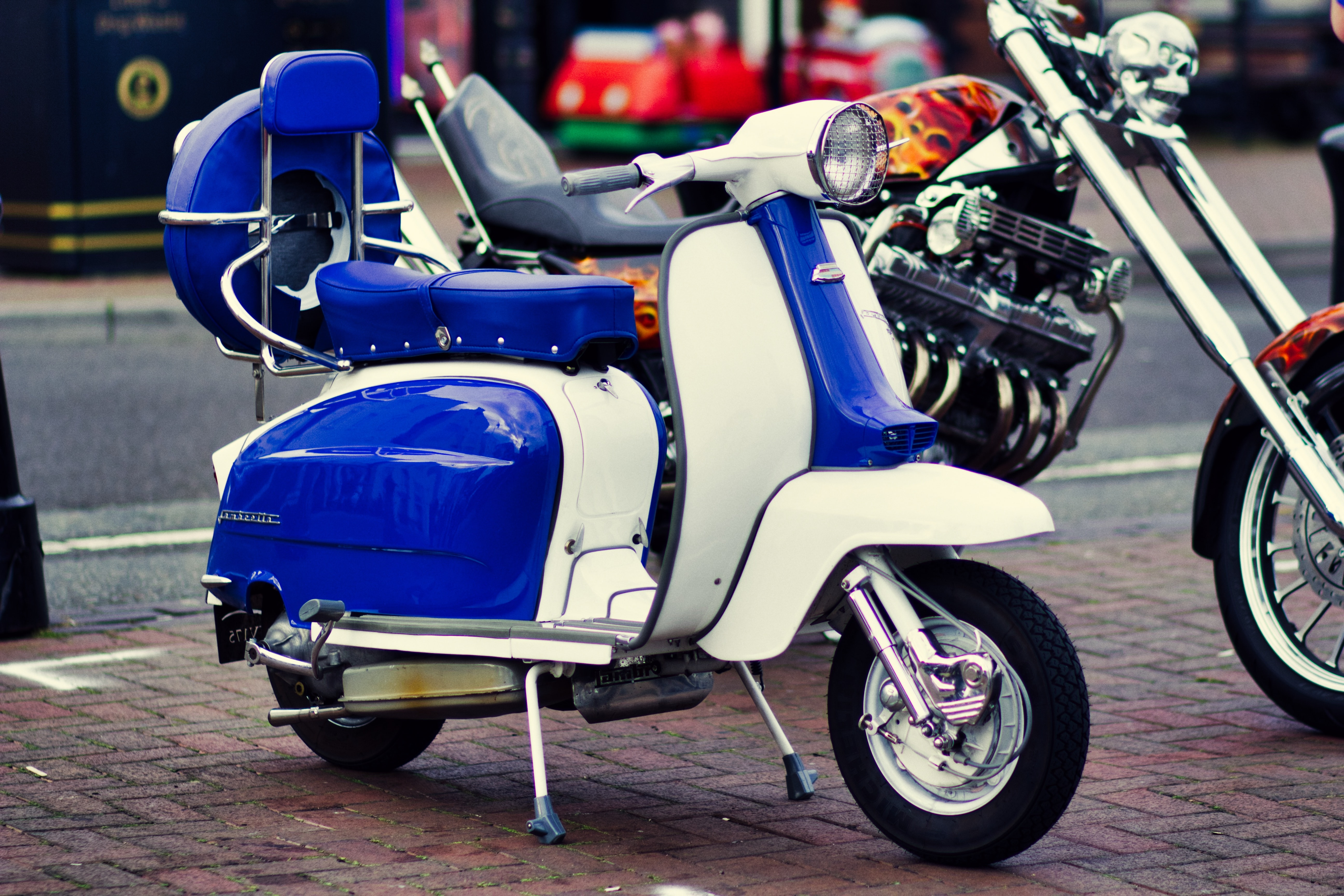 white and blue motor scooter parking beside cruiser motorcycle