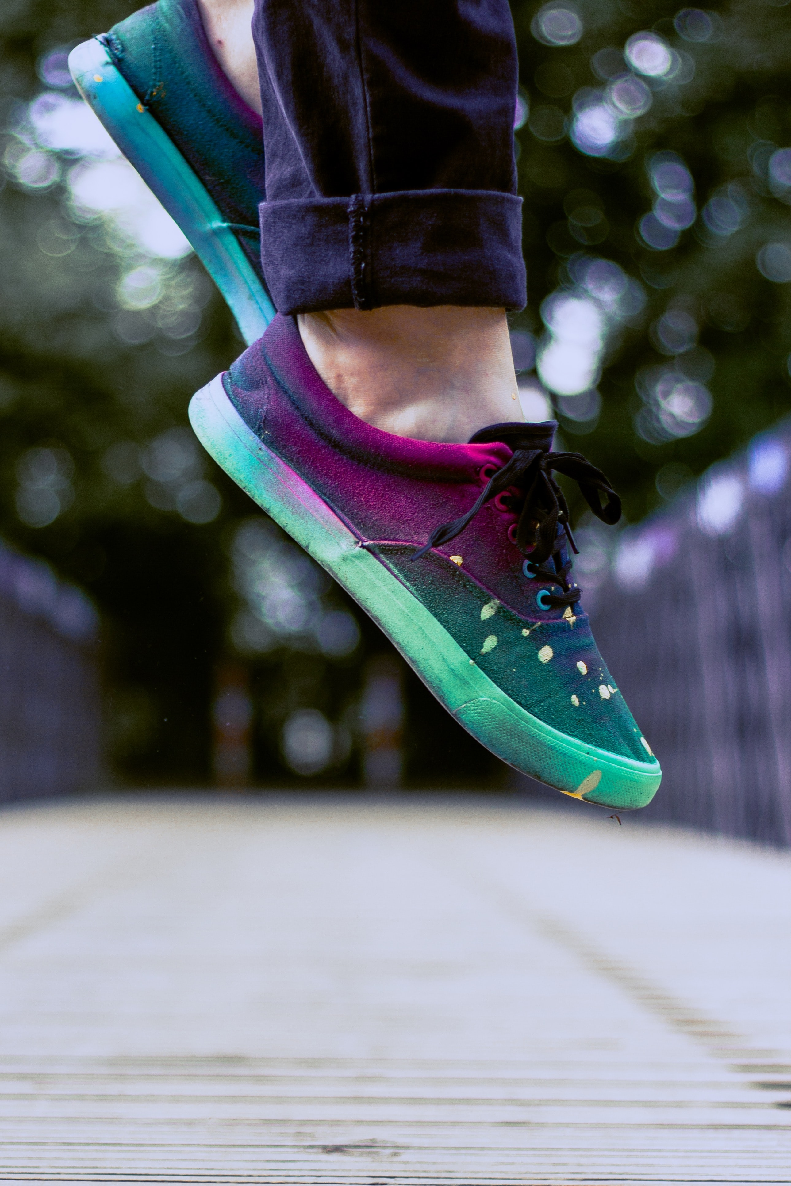 selective focus photography of person wearing multicolored sneakers while jumping