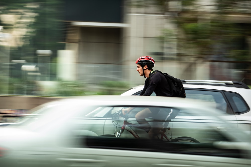 man riding bicycle near car