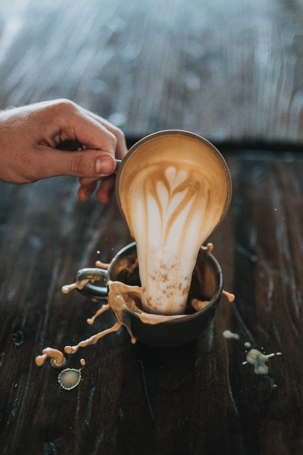 man pouring cappuccino on another cup