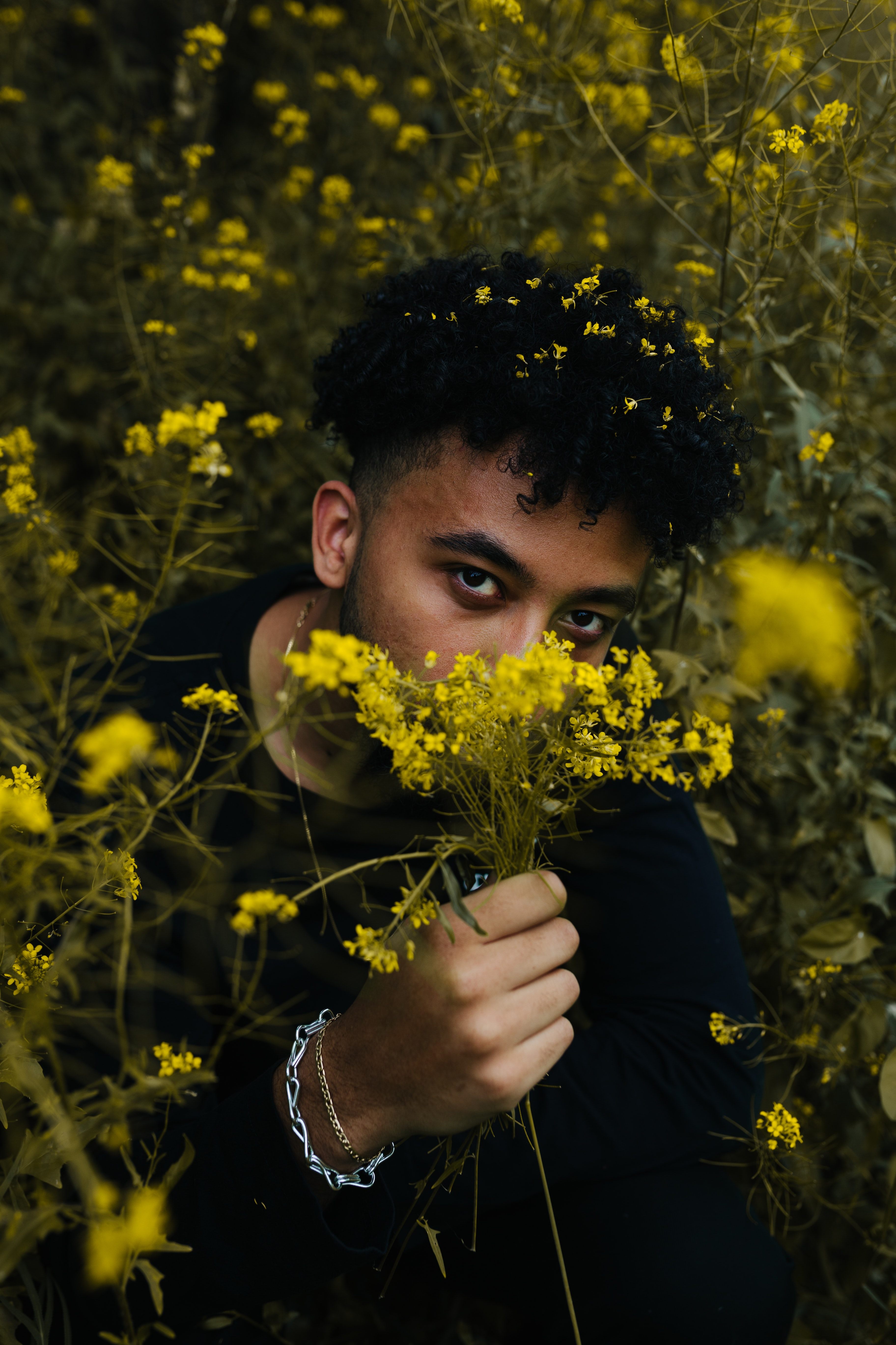 man holding yellow flowers at daytime
