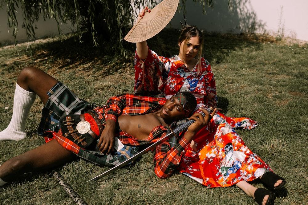 man lying on woman's lap at daytime