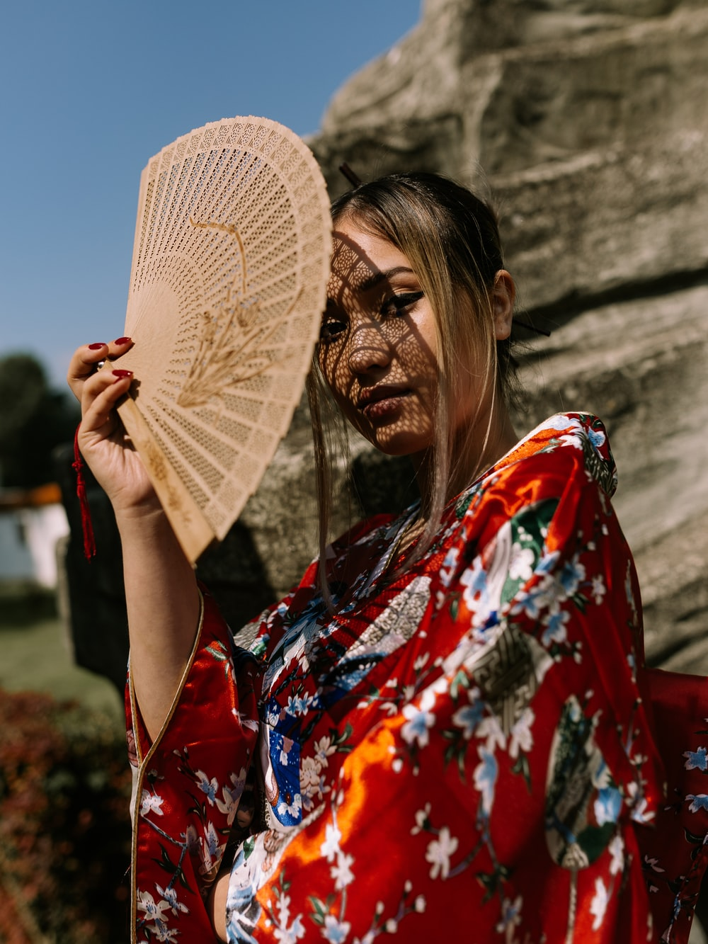 woman in red, white, and blue floral kimono standing and covering her face with wooden hand fan