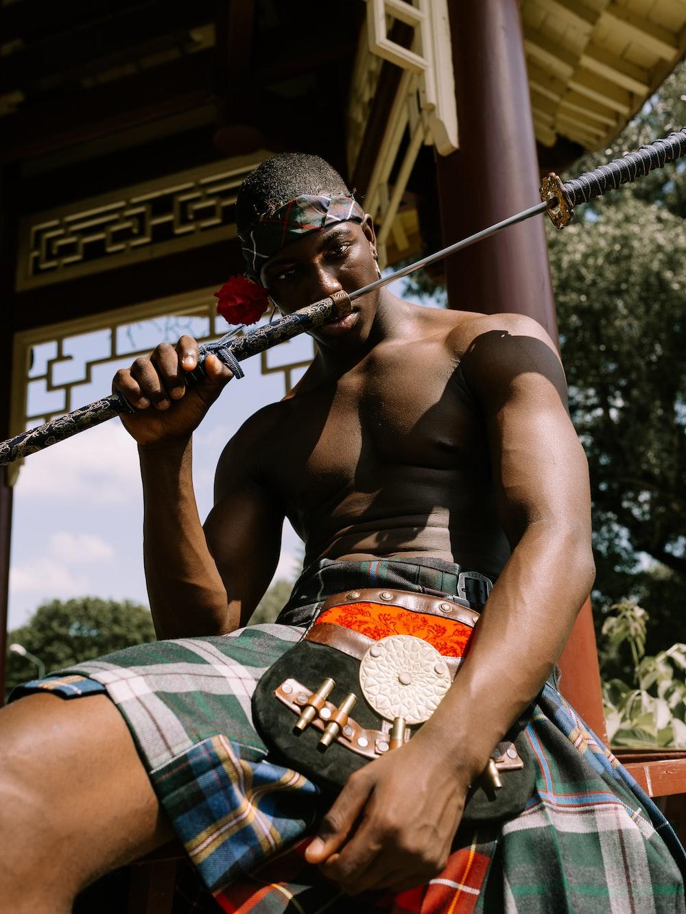 sitting man holding sword near brown post