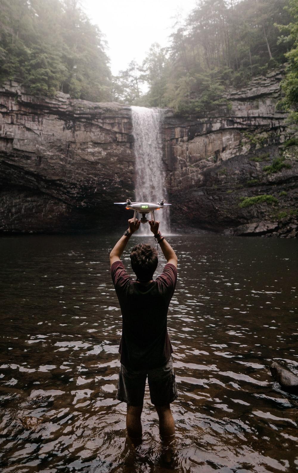 man holding drone facing waterfalls