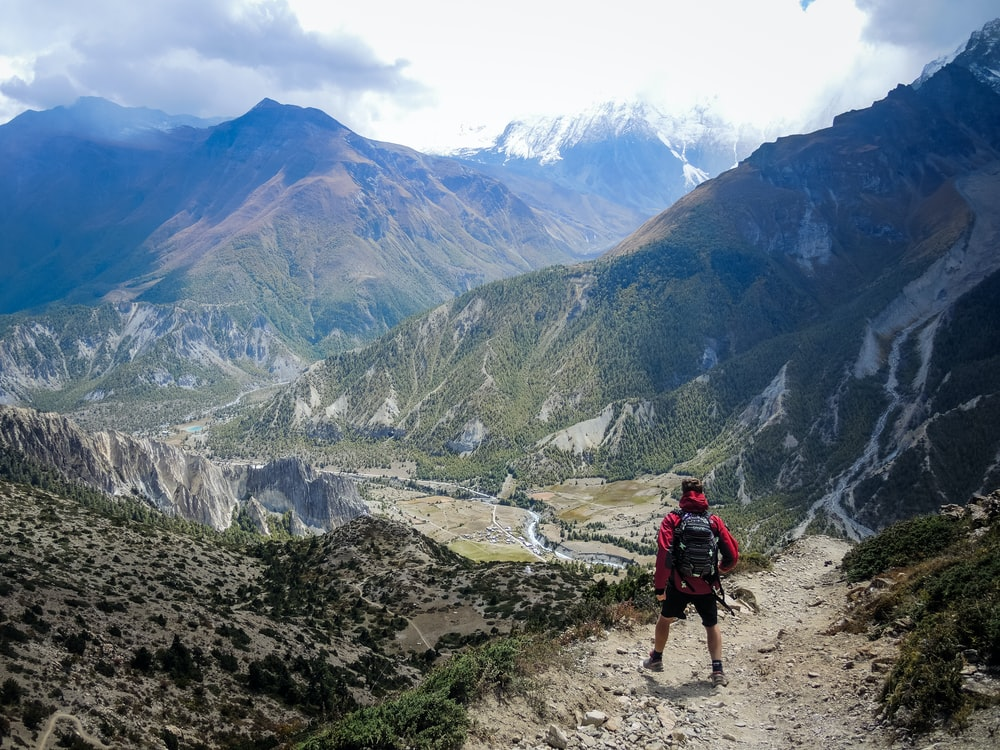 person in red top waling beside mountain
