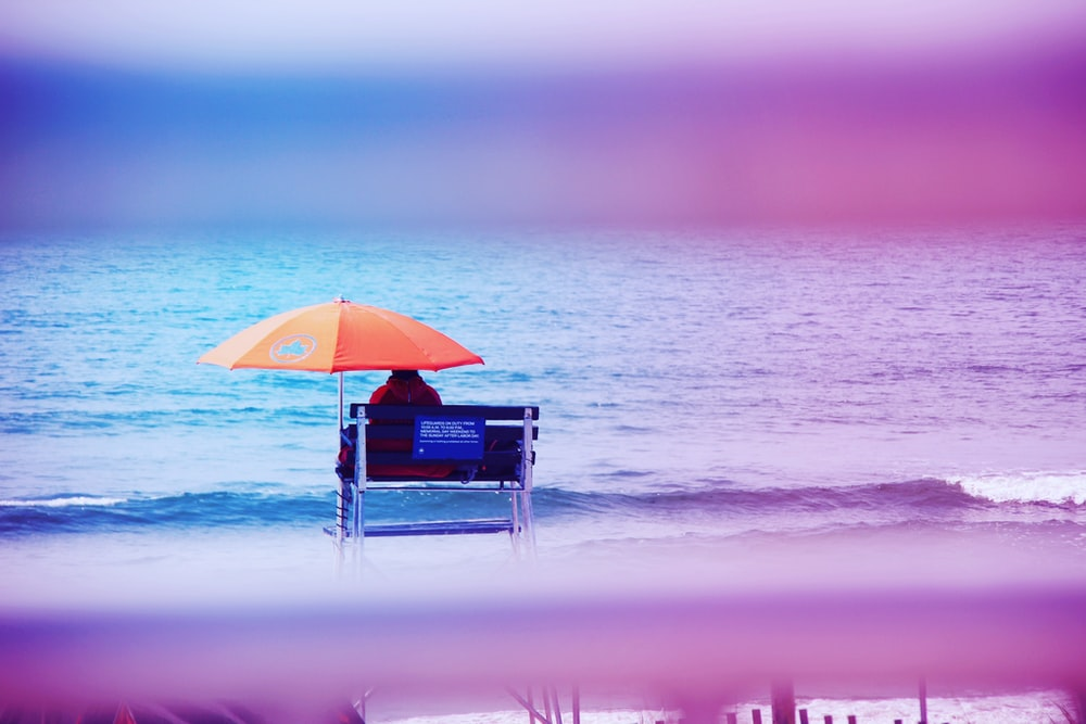 person sitting on lifeguard tower near shore