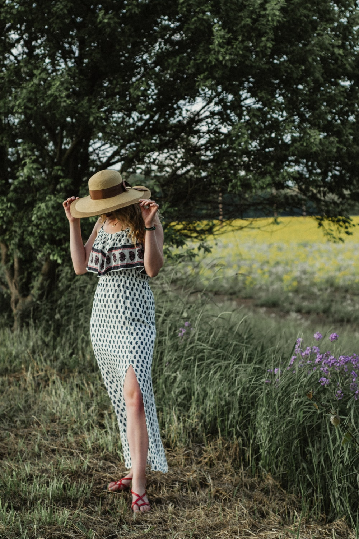 woman holding sunhat near grass field