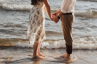 woman holding hands in front of man standing on seashore