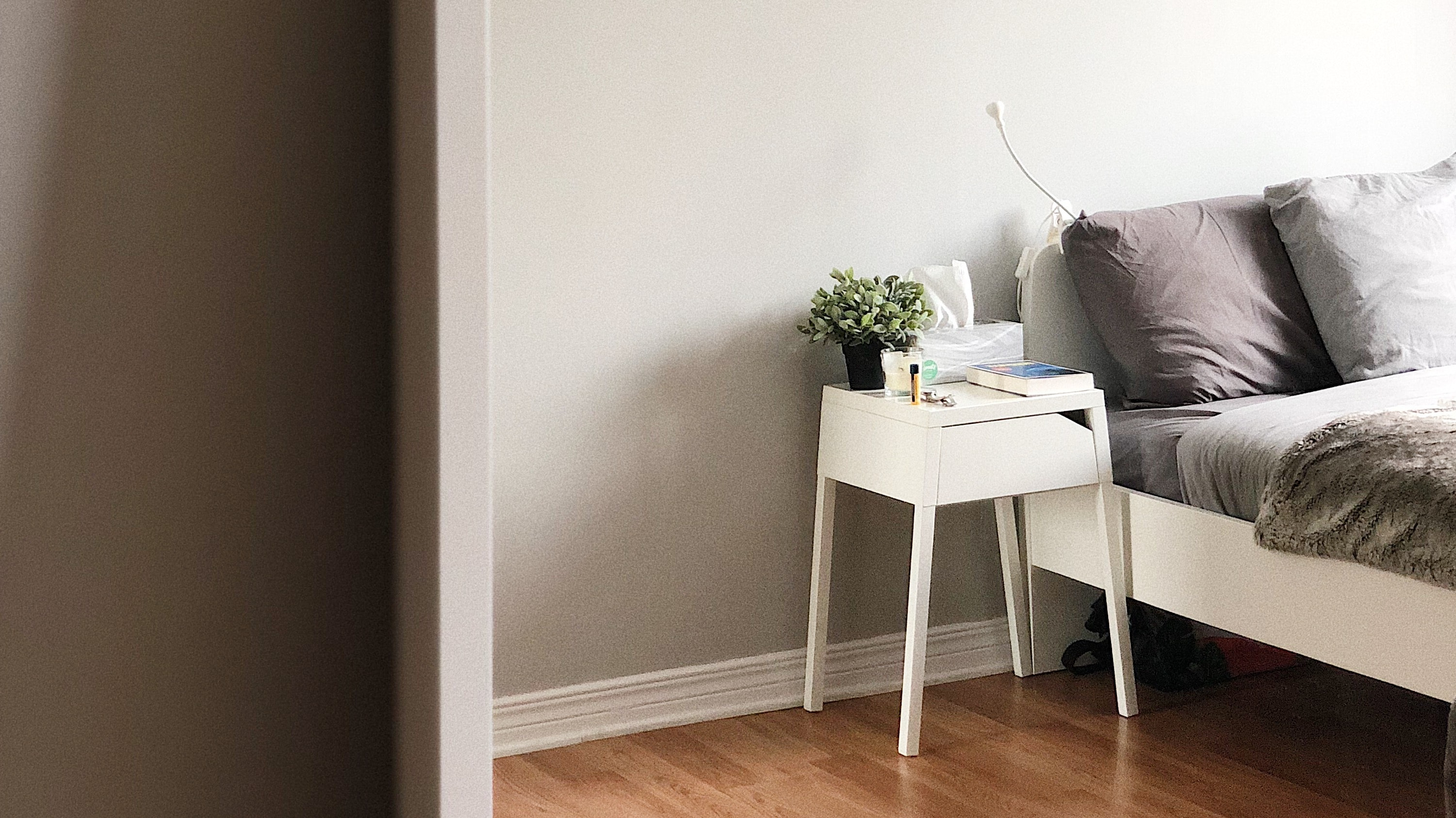 white wooden nightstand beside white wooden bed