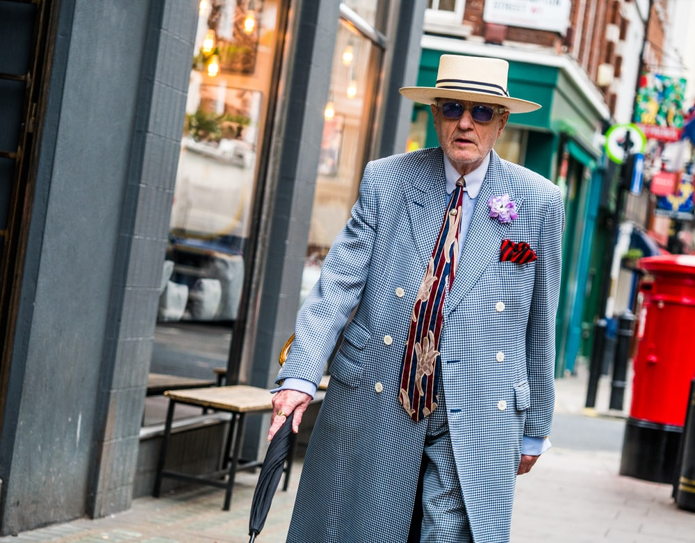 man wearing gray coat holding umbrella walking on the street