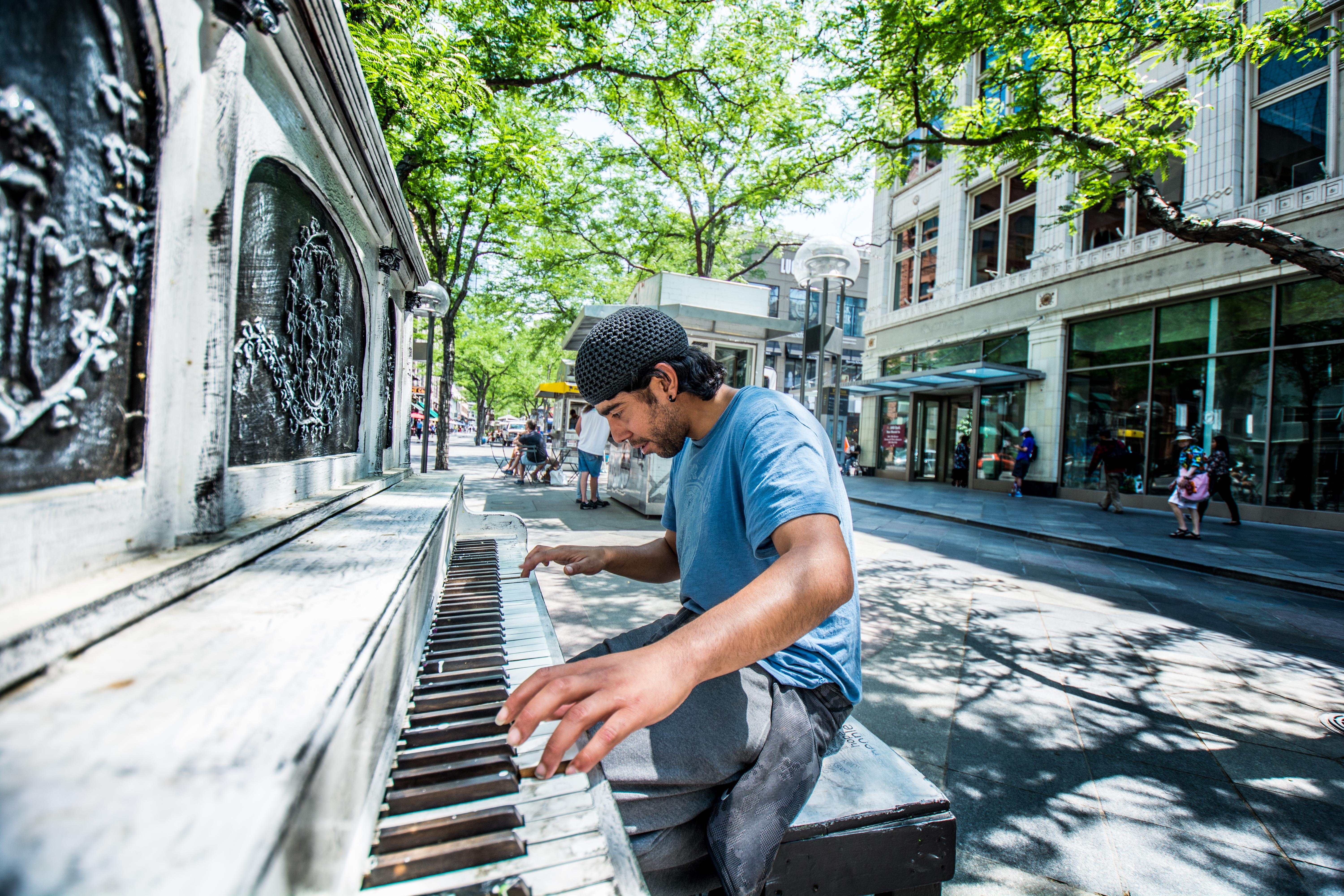 man playing piano on street