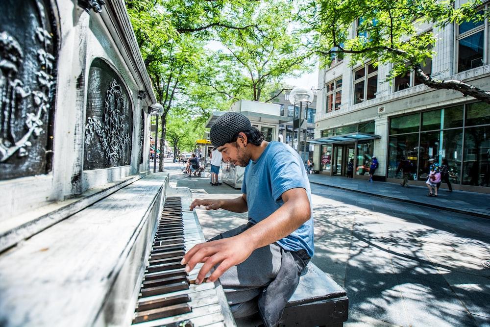 man playing piano on street