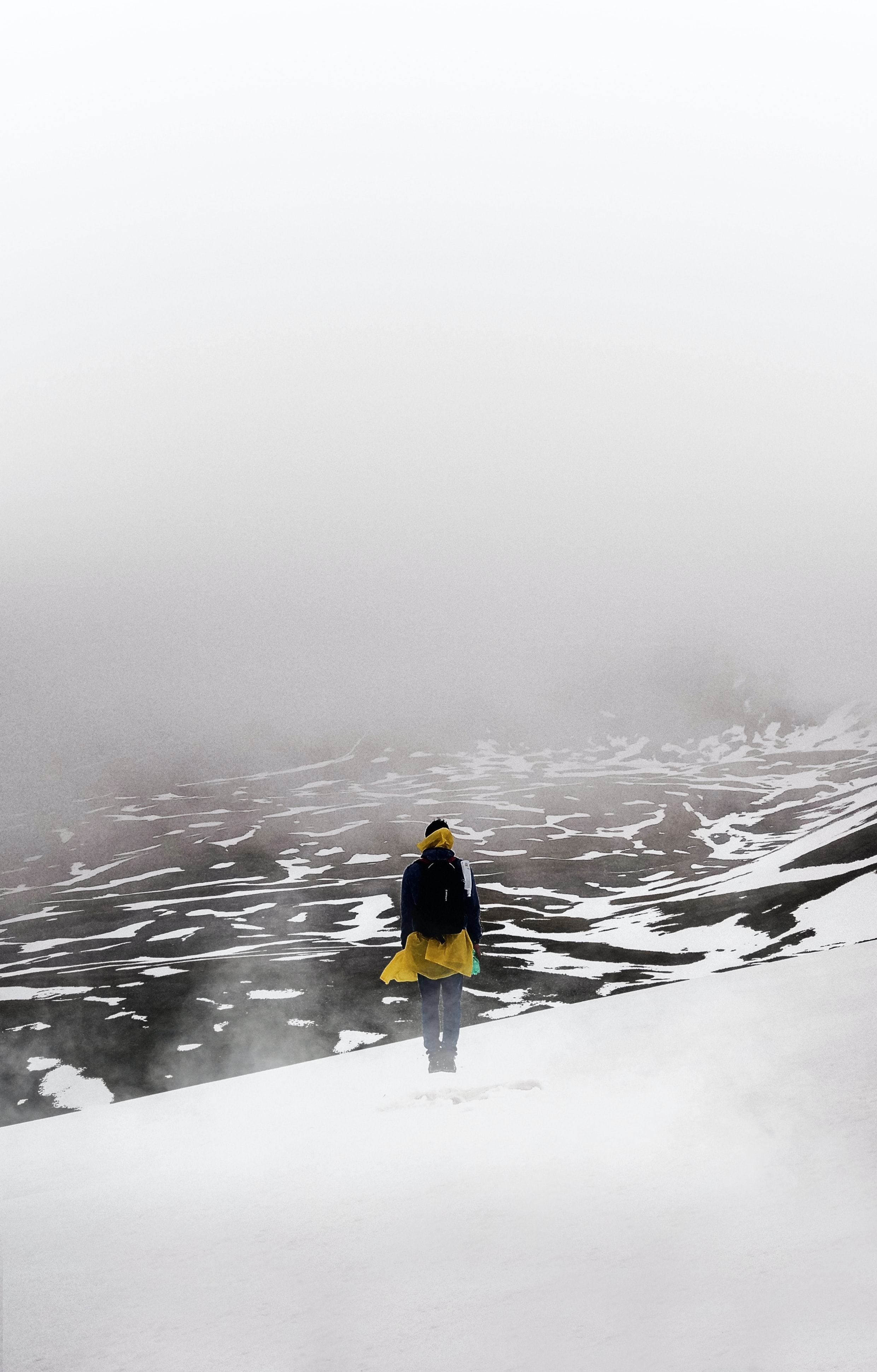 person standing on snow field covered with fog